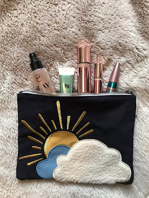 Flatlay of make up spilling out of a make up bag