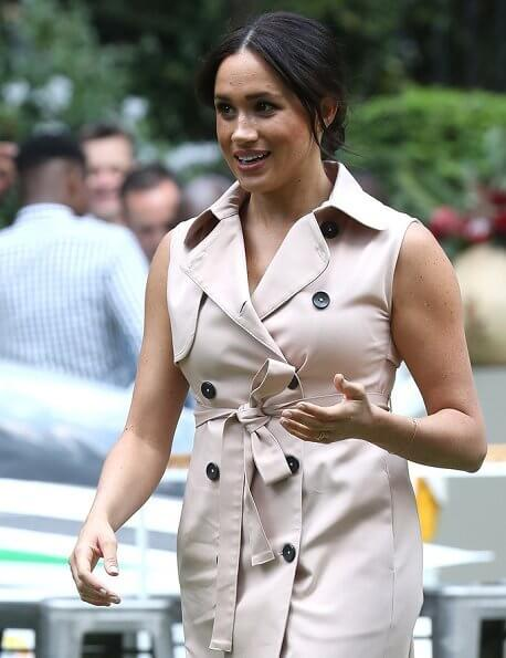 Meghan Markle wore a double breasted trench dress by Banana Republic and suede pumps by Stuart Weitzman