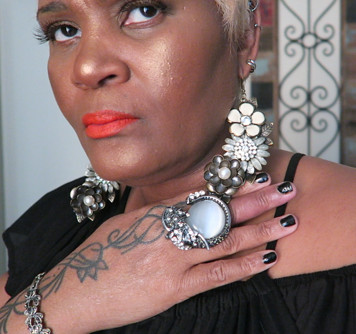 Image: Woman Tangie Bell sharing her earring lookbook with viewers. How to make them with just an earring hook.