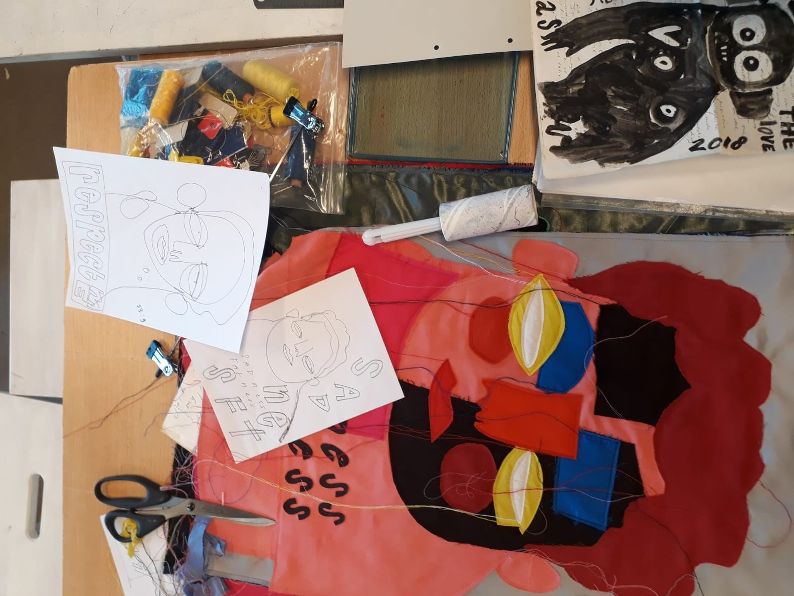 "This picture shows a close-up of one of the quilts Bas Kosters Studio is still working on with the original drawings besides it. It depicts a face in red, pink, black, yellow and blue, with some words next to it (""sadness"")."