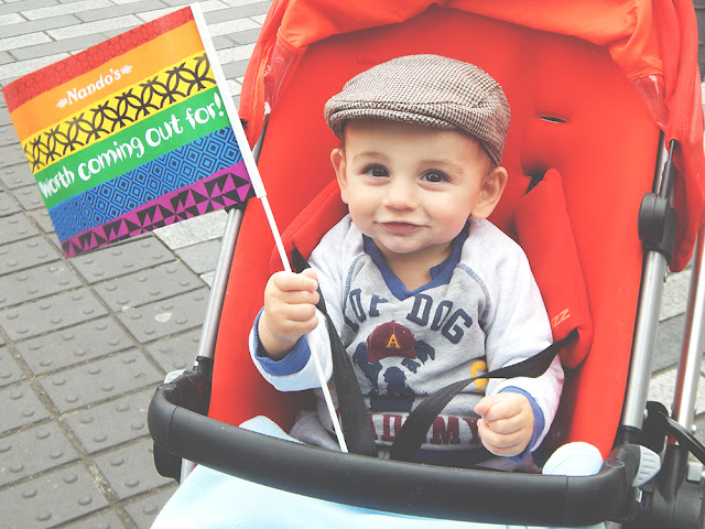 small child holding a rainbow flag and smiling