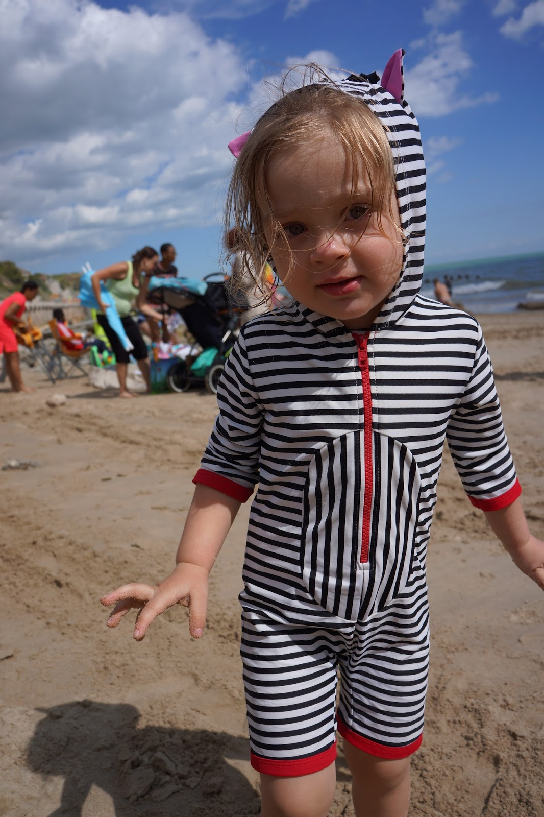 toddler wearing a lilly and sid zebra swim suit on a beach