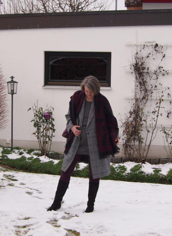 Graues Strickleid und Glencheckmantel mit kühlem, dunklen Rot als Akzentfarbe kombiniert