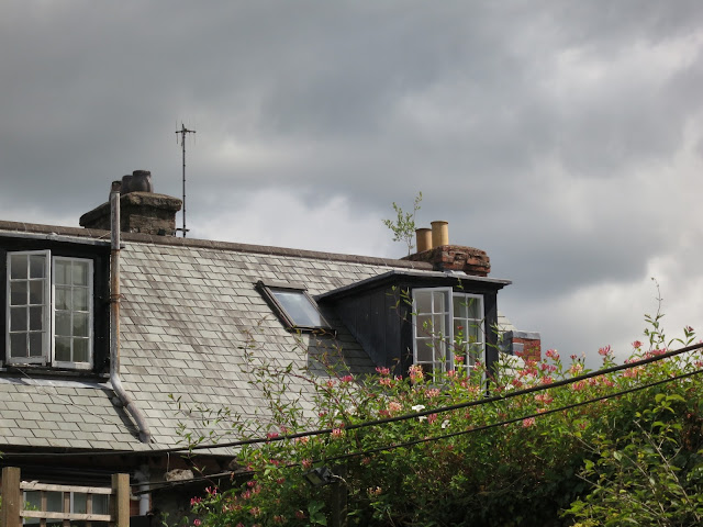 Grey tiled roof, casement windows, honeysuckle, grey sky.