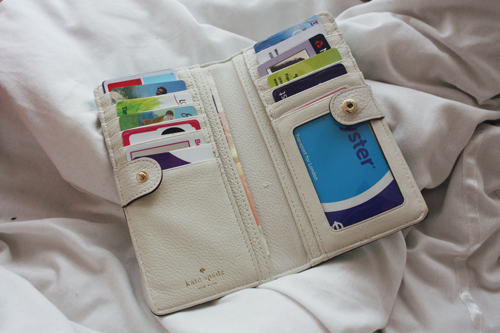 mikas pond stacy wallet by kate spade lying open, revealing several loyalty and debit cards, as well as a london Oyster card