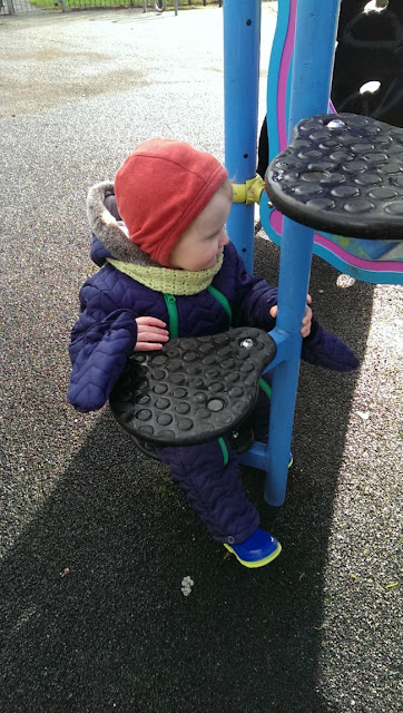 toddler sat on play equipment