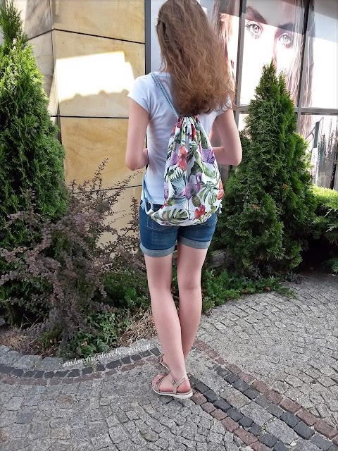 Biały T-shirt, jeansowe krótkie spodenki, beżowe sandały, plecako worek uszyty przeze mnie