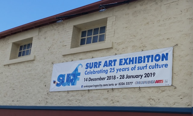 "The long, thin, horizontal banner is pinned beneath two windows on the side of an old limestone building. It reads: ""SURF ART EXHIBITION Celebrating twenty five years of surf culture 14 December 2018 - 28 January 2019. Facebook: onkaparingacity.com/arts or 8326 5577 Onkaparinga Arts.""  The Surf Exhibition logo appears on the left hand side of the banner.  The heritage building is painted cream on the top half with a heritage brown colour for the lower portion of the building and the roof guttering.  A blue horizontal stripe demarcates the cream and brown.  A blue sky is seen in the top left corner."