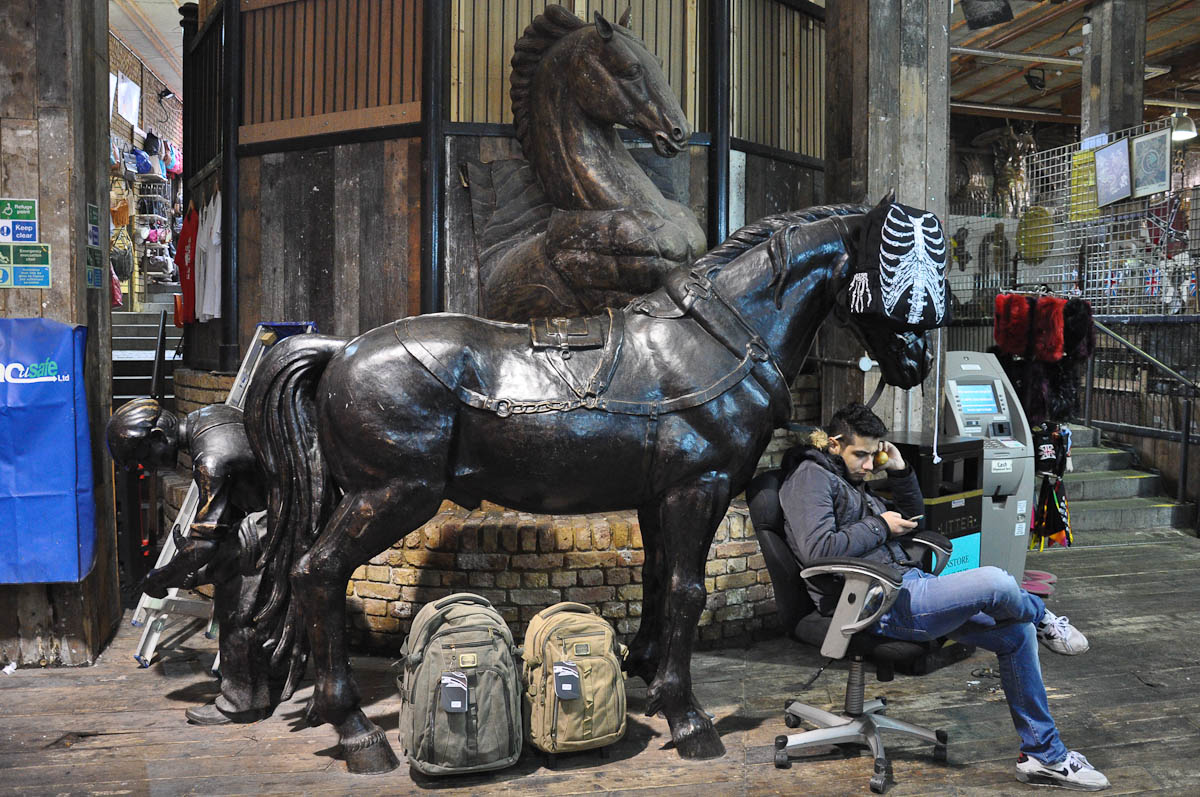 A market trader checking his phone by statue of horses, The Stables Market, Camden Town, London, England