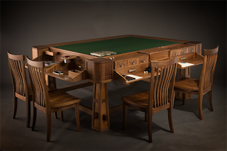 A deluxe gaming table, with recessed top to prevent dice from rolling off the edge, green felt cover, and fold-out writing surfaces that open to reveal drawers, cup holders, shelves and cubbies, and all sorts of other goodies, with two chairs on each side.