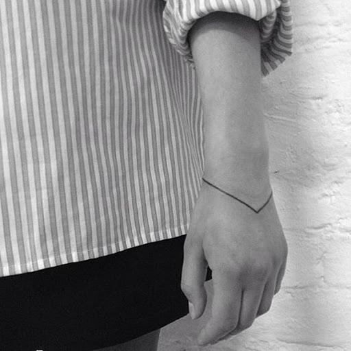 Uma fina linha preta funciona como uma pulseira e atende a um ponto em que a peça se conecta acima do utente com a mão esquerda.