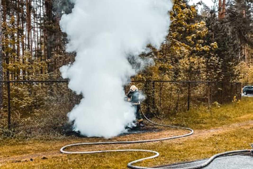 Balti dūmi ceļas no ugunsgrēka, kuru dzēš ugunsdzēsēji