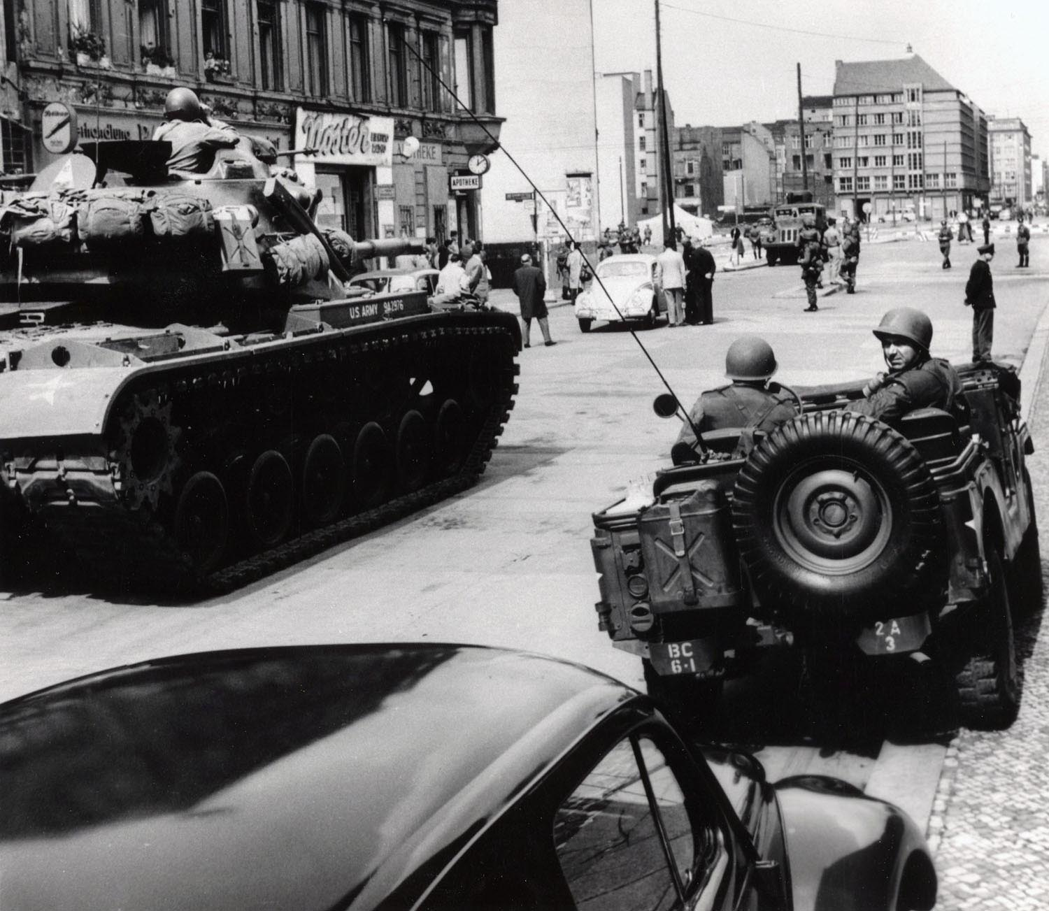 American tanks face an East German water cannon at Checkpoint Charlie.