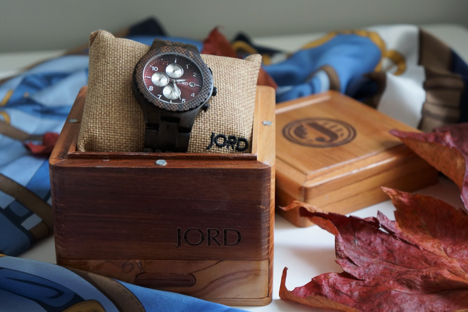 JORD men's wooden watch with dark sandalwood in a box with a blue scarf and red leaves behind it