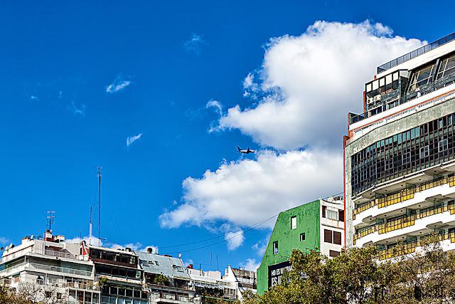 Avión volando hacia las nubes del cielo azul