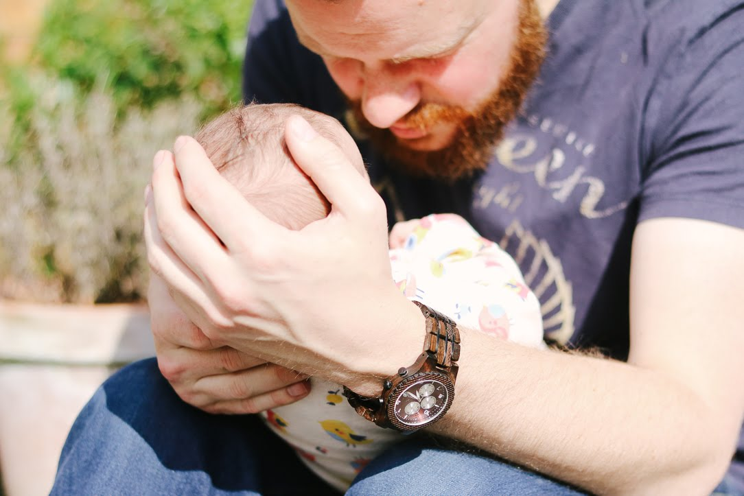 a close up of a man's hands holding a newborn baby. the man is wearing blue jeans, navy shirt and a dark wooden watch