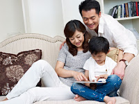 parents reading to child on tablet