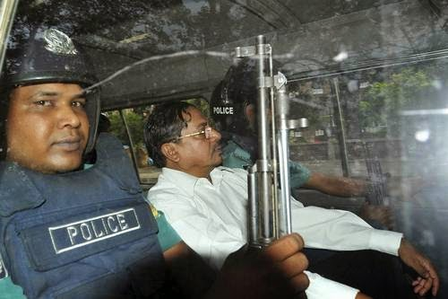 Muhammad Kamaruzzaman leaves a court escorted by policemen in Dhaka, Bangladesh, in May 2013.