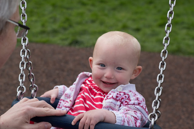 A smiling baby on a baby swing in a pink and white striped dress