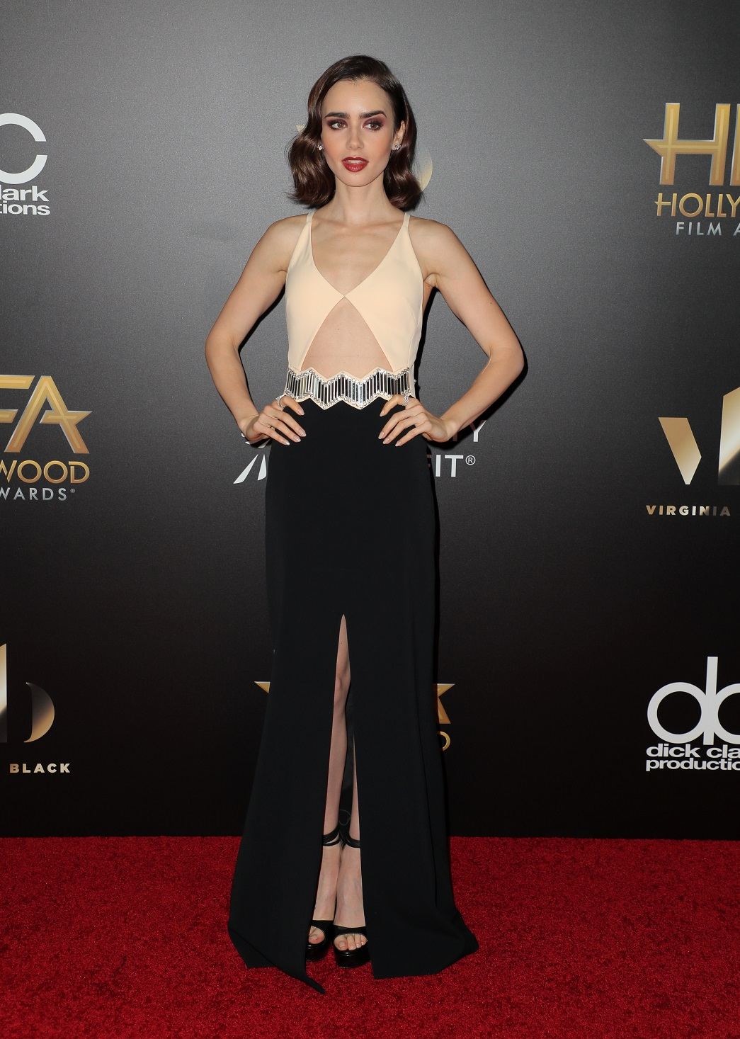 Lily Collins channelled old Hollywood glamour in an eclectic cream and black dress slit to the waist as she arrived at the Hollywood Film Awards on Sunday night