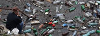 Man fishing on sandy shore full of discarded plastic bottles