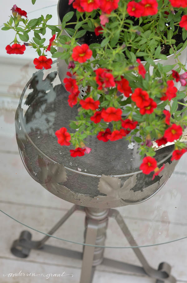 A rusty plant stand can be repurposed and painted to create an outdoor accent table for your deck. |  www.andersonandgrant.com