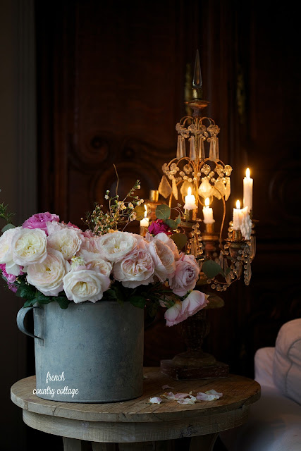 Drippy candles with zinc bucket filled with roses