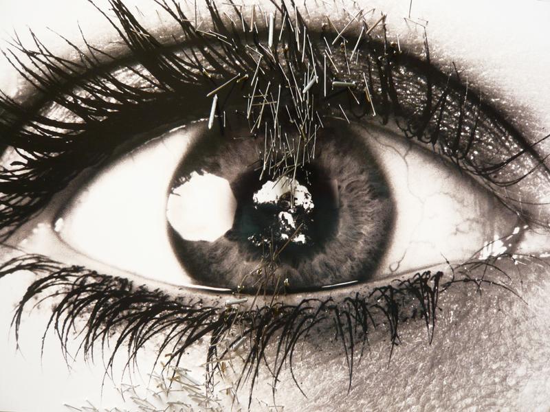 Une photo d'un oeil ouvert reflète une image de la bombe H. La photographie est criblée de pointes et d'aiguilles.