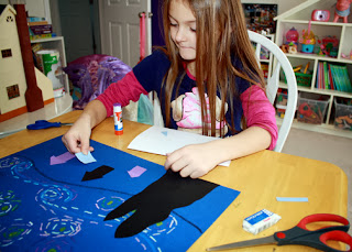 Tessa cut and glued shapes for the trees and houses from colored cardstock. Afterward, she finished up with oil pastels.