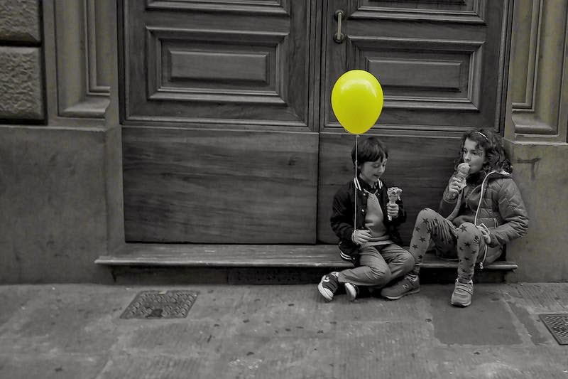 two kids eating an ice cream in Florence, one of them holding a yellow balloon