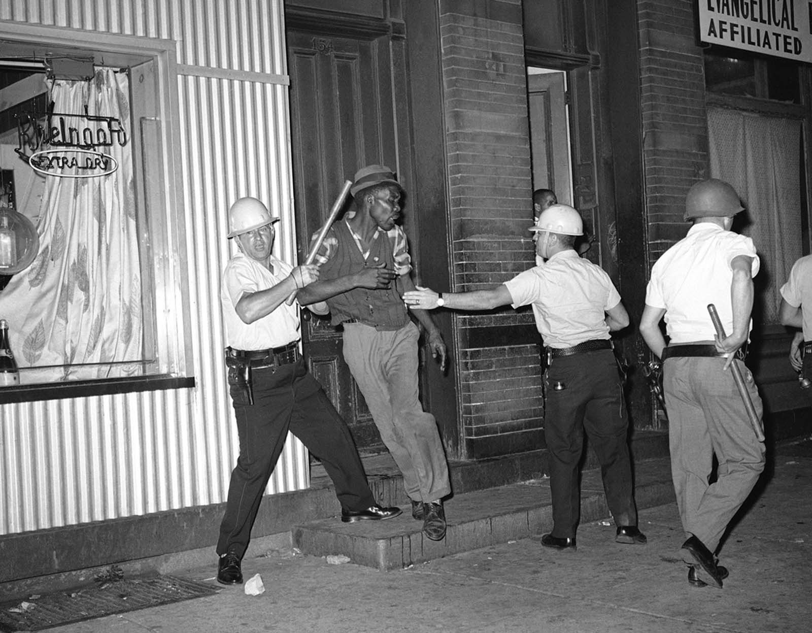 Holding their clubs in their hands, two Elizabeth policemen struggle with a man as they try to move him from area of rioting in Elizabeth, New Jersey, on August 12, 1964. Police had to fire shots in the air and use their clubs to break up the crowd of 300 to 400 white and black youths tossing bricks, bottles and gasoline bombs. It was the second night of violence in Elizabeth and Paterson, New Jersey.