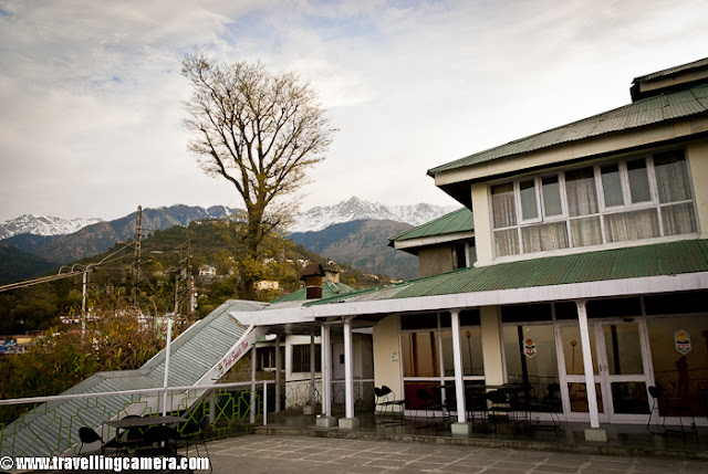 During beginning of this year, I visited Dharmshala for covering finals of Cricket Mahasangram and HPCA(Himachal Pradesh Cricket Association) had arranged for stay in Dhauladhar Hotel, which is just in the middle of Dharmshala Market.This is a view of backside where Dhauladhar Hotel has some open dining area with wonderful view to the valley !!I took Volvo form Delhi and reached early in morning. Dhauladhar Hotel is at walkable distance from Bus stand but since I had more stuff to carry, so got a taxi at very reasonable tariff (50 Rs :) )I entered into the room and it was decent, although very old. Personally I am not very choosy unless things are not neat and well placed. So I found this room a good place to stay for me. Service was also good, although I had an extra advantage of being able to speak in Himachali ! I loved the woodwork there. I have heard of Kangra Suite in this hotel which is considered as best place.Here is a view of some colony from open dining area of Dhauladhar Hotel in Dharmshala !!! This hotel is approximately 4 kilometers far from Cricket Stadium constructed by Himachal Pradesh Cricket Association.Another view of a valley from Dhauladhar Hotel in Dharmshala, Himachal Pradesh, INDIA. Usually people prefer to stay in Mcleodganj as compared to Dharmshala Town.Hotel corridor which connect most of the rooms on second floor. The first suite on the right is Kangra Suite !!!This is back side of Dhauladhar Hotel in Dharmshala ! This could have been better maintained. There is enough space to make a garden as well !!!Another view of a valley from Restaurant of Dhauladhar Hotel in Dharmshala !!!Dhualadhar Mountain ranges are clearly visible from this hotel and people prefer to have their meals in open dining area !!!This is restaurant of Dhauladhar Hotel, which can be seen empty most of the times. It's not that people don't visit, but people prefer to sit in open dining area.There is a small parking area in front of main entry of Dhauladhar hotel, but it seems currently residents of Dharmshala use it in better way :)Here is another corridor in Dhauladhar Hotel, Dharmshala. Monkeys can be seen in these corridors as whole area is not very well closed. So they enjoy walking inside this hotel to see different types of tourists !!! Soon after checking in at Dhauladhar, I had to reach stadium. I thought of walking down to the stadium and few gentlemen offered me lift but I wanted to see other things on the way. Photograph above shows dense Dharmshala town where everyone want to live !!!A photograph of road going down towards HPCA cricket stadium. Dharmshala market is mainly spread around this road only. There are some main offices are also on the way to stadium !!!Another view of Dharmshala valley full of colorful houses !!!Another HPTDC hotel in Dharmshala Market !!Roads are really well maintained inside the town. Overall roads in Himachal Pradesh are far better than what we daily see in Noida.Here is last colorful photograph from Dharmshala !!! Overall stay at Dhauladhar Hotel was good and I love HPTDChotel.