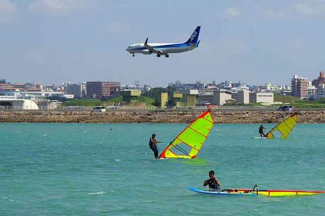 plane landing over windsurfers