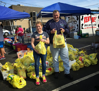 Erin Lynch, Franklin Food Pantry executive director, and Mike Catalano, Franklin Postmaster, lend a hand in the Stamp Out Hunger food drive for the Franklin Food Pantry