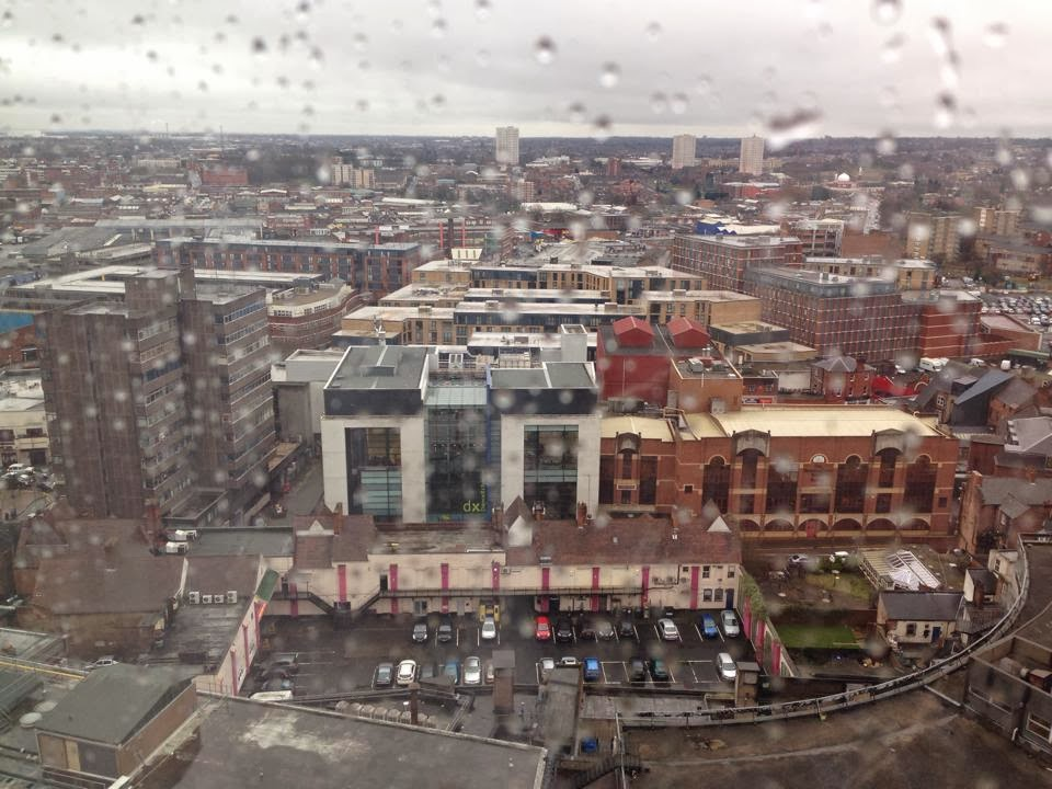 view from our high balcony window. raindrops can be seen running down the pane and Birmingham city centre can be see past that