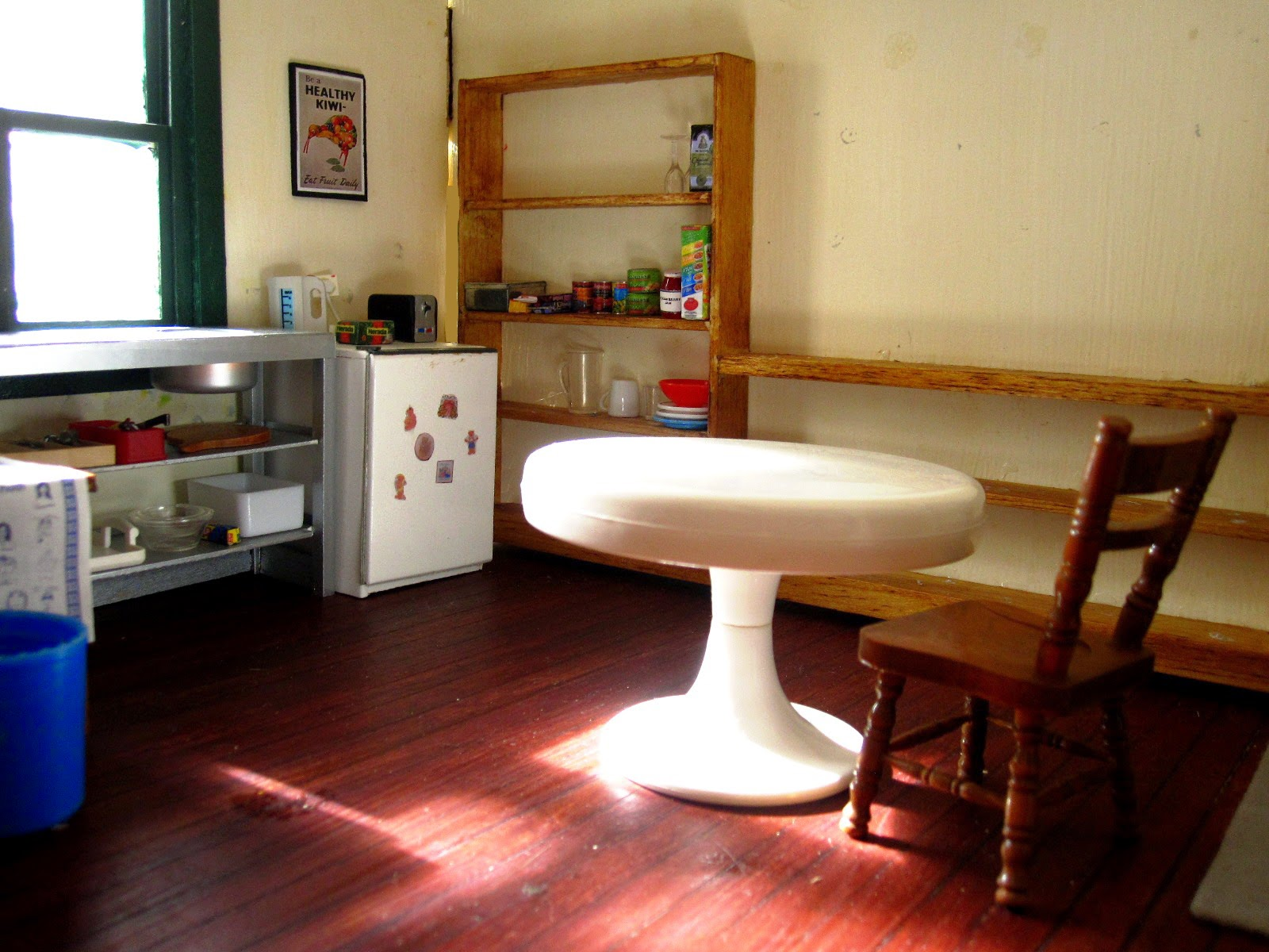 Interior of a modern miniature holiday house kitchen, with a round white table in the foreground.