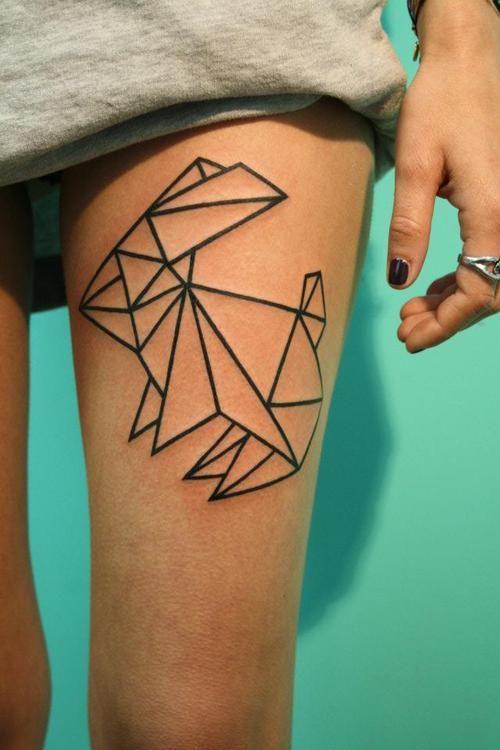 Vemos las piernas de una koven, lleva minifalda y en su muslo lleva un tatuaje de conejo origami