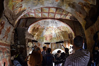 "People look at the restored fresco ""dei Fornai"" (bakers) cubicle, during a visit after the restoration of the catacomb of Santa Domitilla, in central Rome, on May 30, 2017 [Credit: AFP/Andreas Solaro]"