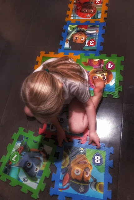 Paw Patrol playmats being assembled into a Hopscotch by a young girl