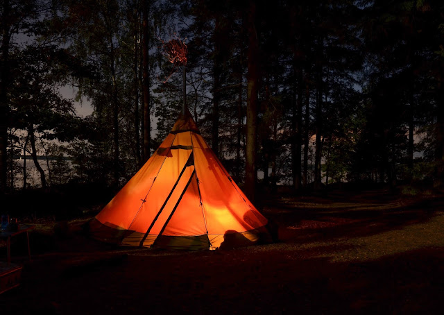 A tippee style tent, lit up in the darkness of a wood