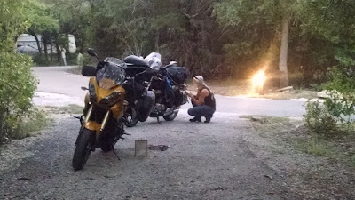 Bikes parked at a woodsy campsite, Skipper kneeling beside Hades, her face blended into the trees behind