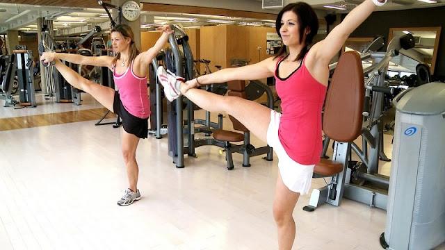 dua orang perempuan sedang berolahraga di gym
