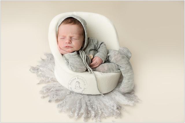 Sleeping newborn in a white posing pod chair