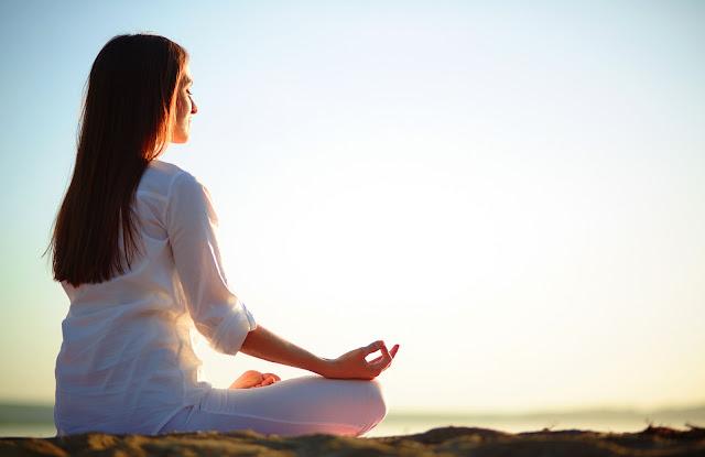 Mujer vestida de blanco en posición de meditación