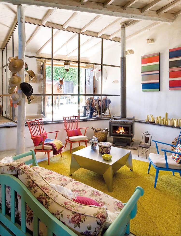 detalle del salón de una casa rústica con muebles de diseño, un tronco en el salón, y mobiliario de colores variados