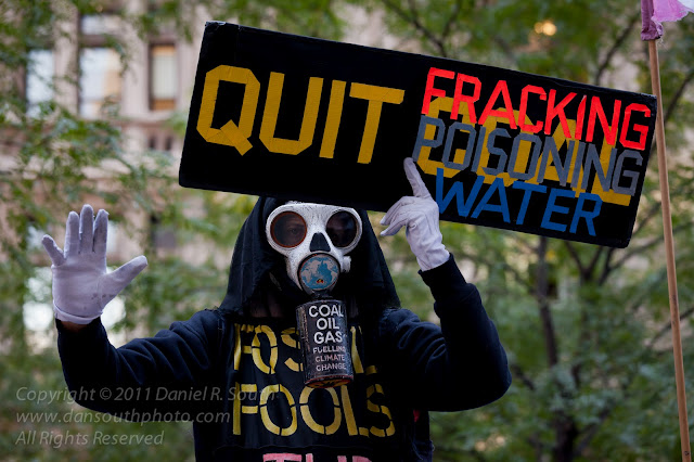 a photograph of an occupy wall street fracking demonstrator in a gas mask