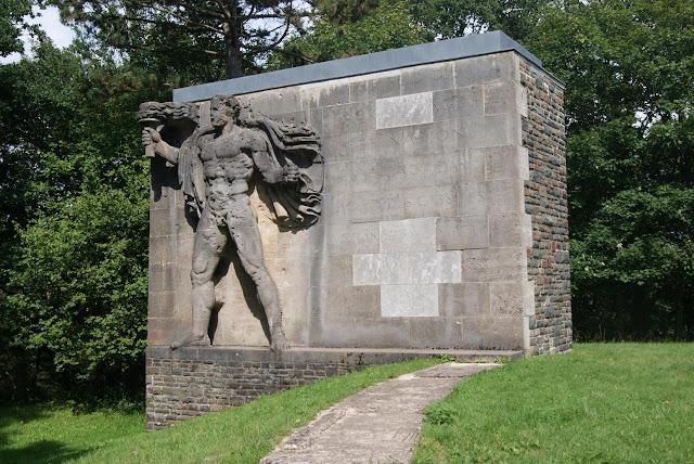 Eine große Steinwand, in die ein muskulöser Mensch mit einer Fackel gemeißelt ist. Daneben steht eine, teilweise entfernte, Inschrift
