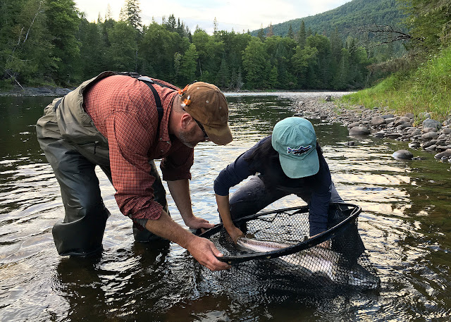 David Bishop and Hyun with a salmon in the net, Grand Cascapedia, Quebec