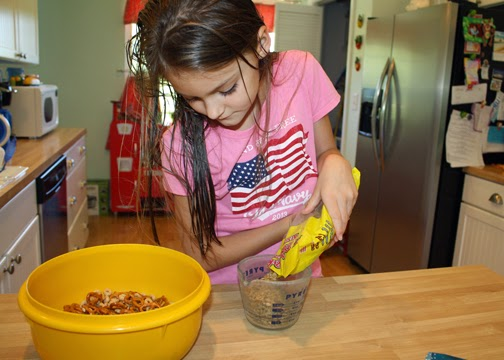 Tessa measured out about a cup of each ingredient for her trail mix and then stirred it all together.