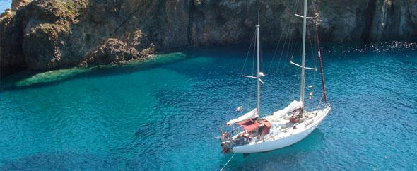 Les bateaux et principalement les voiliers, ici un bateau dans une crique cristalline en Corse est au mouillage, en arriêre plan la côte escarpée et sauvage de Sartene, un nouveau cap